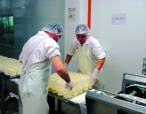 On retire les fromages des moules en plastique qui les maintenaient